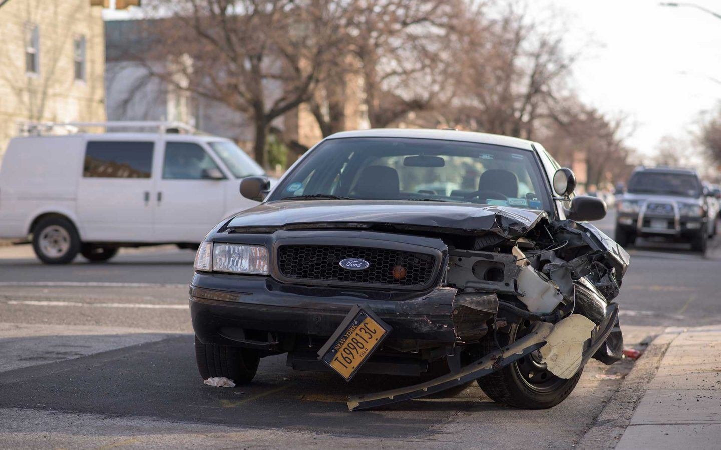 black ford car after a car accident with damaged front right bumper
