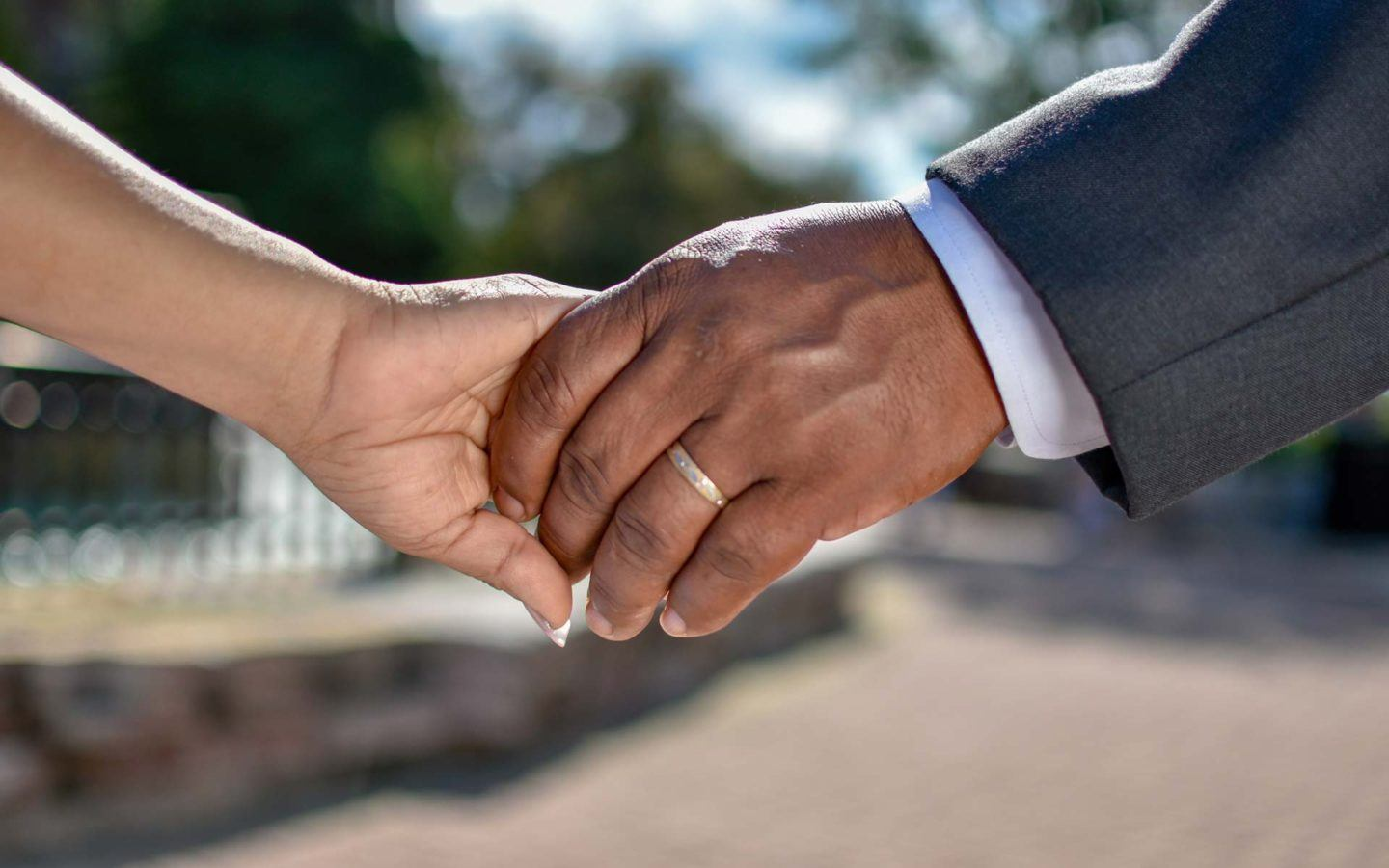a close up photo of a couple holding hands featuring the man's wedding band