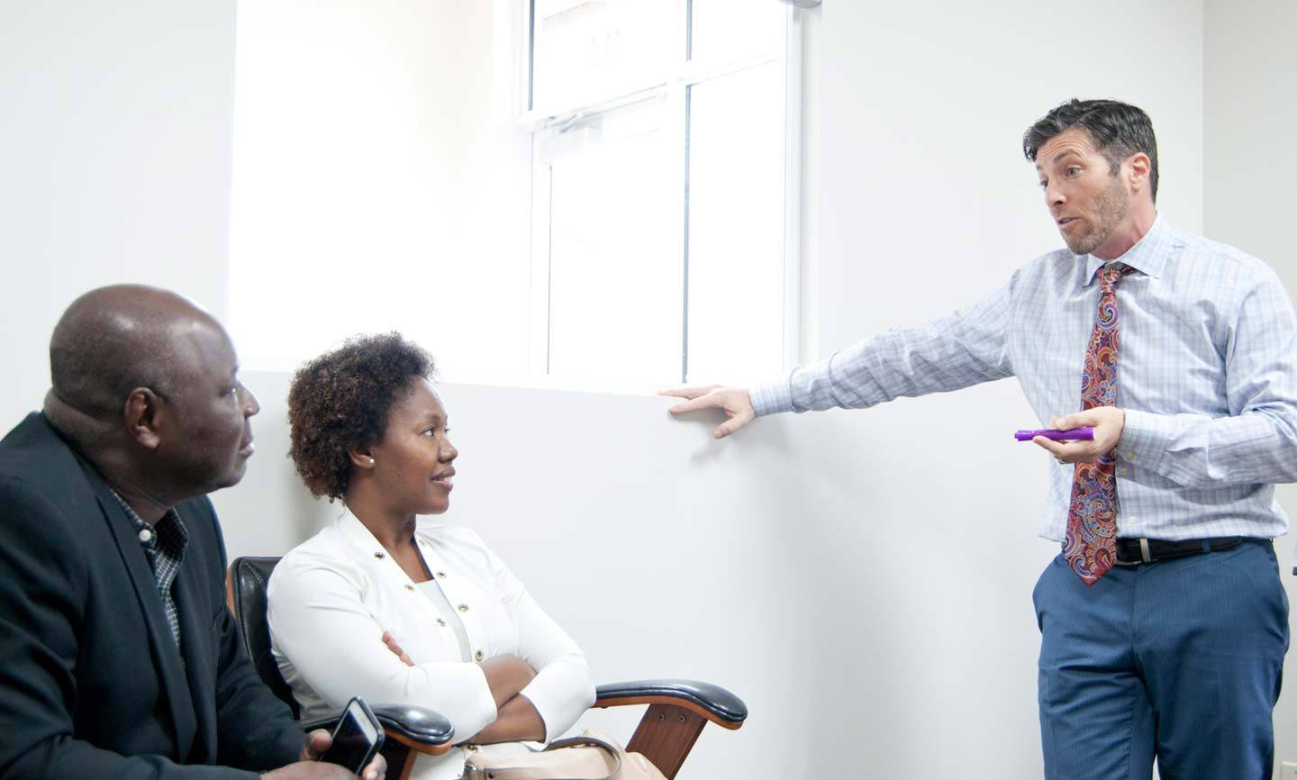 Steve Deitsch speaking with a male and female client in a meeting room
