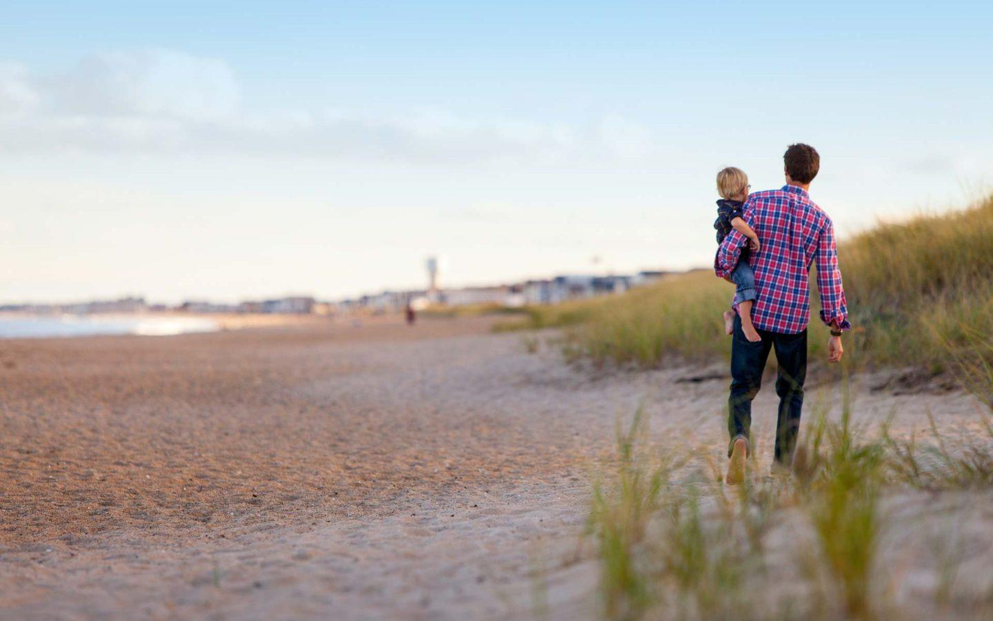 Man in flannel shirt holding his child while walking on a sandy beach