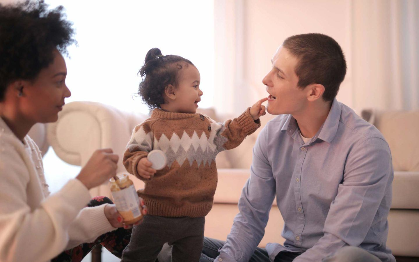baby girl pointing finger at man's mouth, with women holding baby food